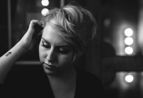 Moody black and white portrait of short blonde hair female.