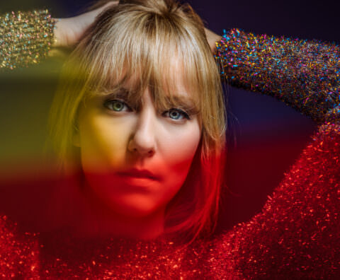Studio photo with Yellow and Red Gels, blonde hair, blue eyes.