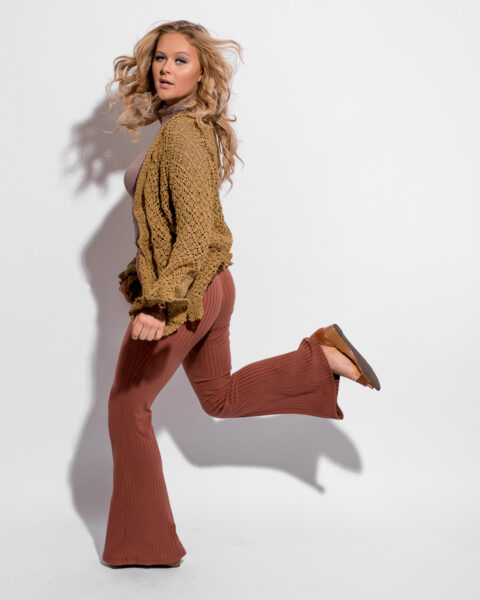 Girl jumping in studio, white seamless backdrop. Target ad vibe. Mustard Cardigan and Rust colored pants