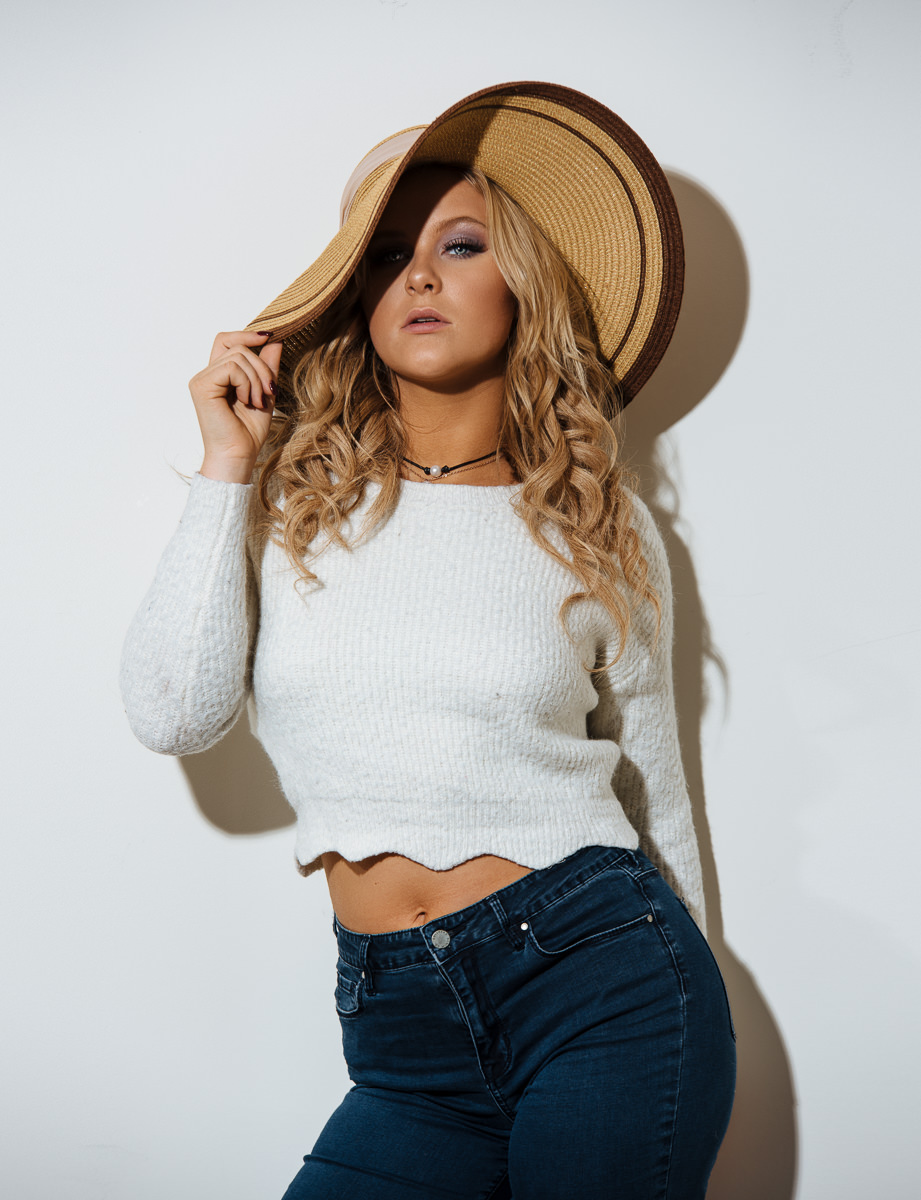 Harsh studio light up against white backdrop. White crop top with brimmed hat and blue jeans. Sassy look.
