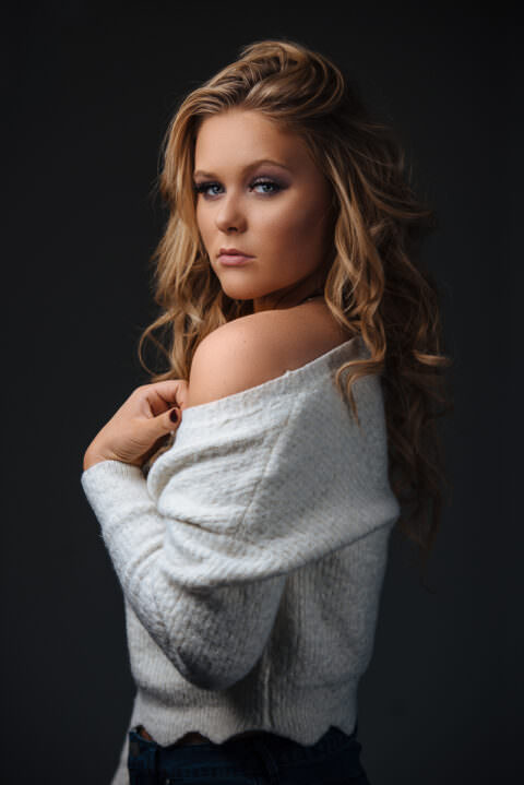 Portrait in studio lit from above. Model wearing white sweater with bare shoulder out. Blonde curly hair.