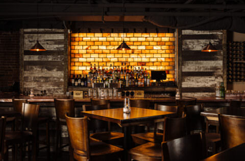 Restaurant bar area with Sea Salt background. Moody lighting and wood panels. Bar top tables