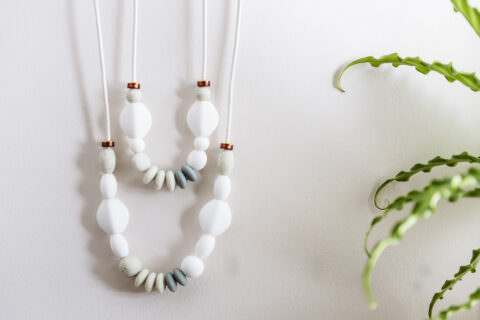 White teething necklace for baby with greenery on the edge of photo