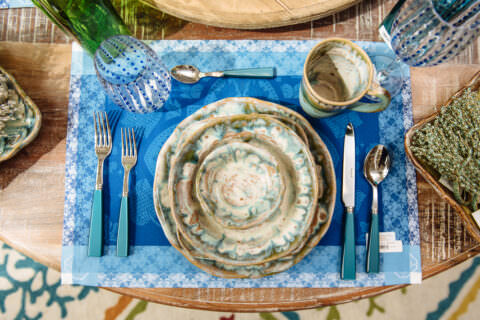 Pottery plates and cup with Silverware with blue handles and a blue placemat shot from above.