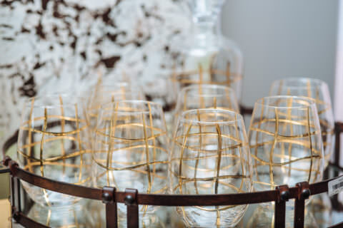 Fancy wine glasses with gold lines making a grid.