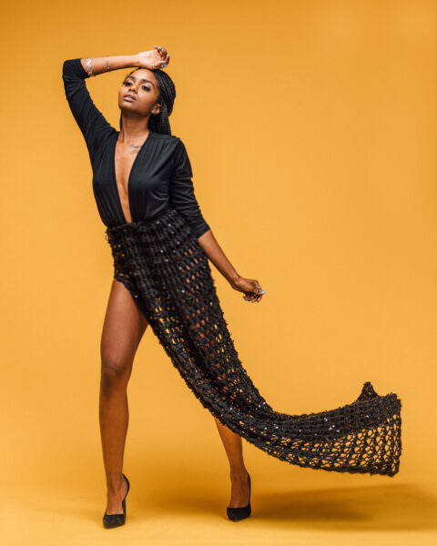 African American model in black crochet flowing skirt with a plunge bodysuit on a savage seamless yellow background