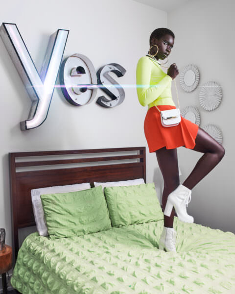 High fashion image of a young beautiful black woman who is wearing neon green top and bright red skirt with heeled white sneaker type of shoes with a white purse. She is standing on a bed with a neon bedspread and sign above the bed that reads YES